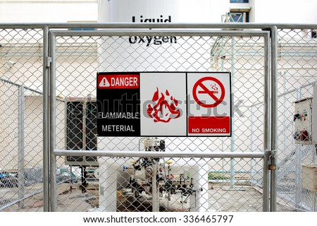 Safety signs warning ( DANGER-FLAMMABLE MATERIAL ) in front of the large Liquid Oxygen tank. - stock photo