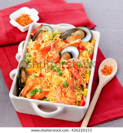 saffron paella with seafood in a white dish on red napkin - stock photo