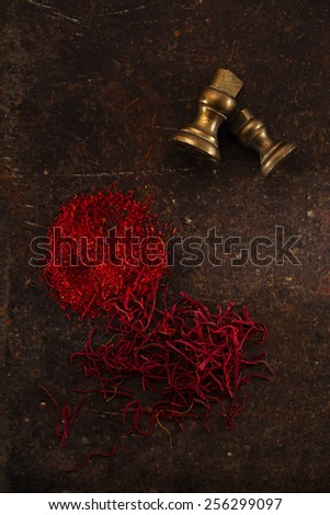 saffron spice in pile threads and powder on old metal background, closeup - stock photo