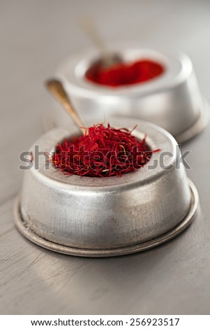 saffron spice threads and powder  in vintage  old dishes,  tin metal background, closeup - stock photo