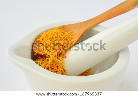 Saffron, tasty and costly spice in porcelain mortar and wooden teaspoon isolated on white background - stock photo