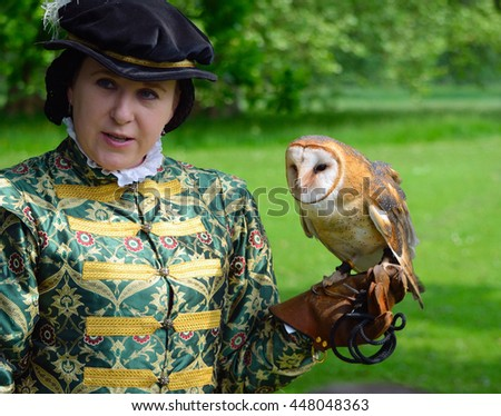 SAFFRON WALDEN, ESSEX, ENGLAND - JUNE 05, 2016: Woman wearing Elizabethan costume with Barn Owl on Gloved hand.  - stock photo