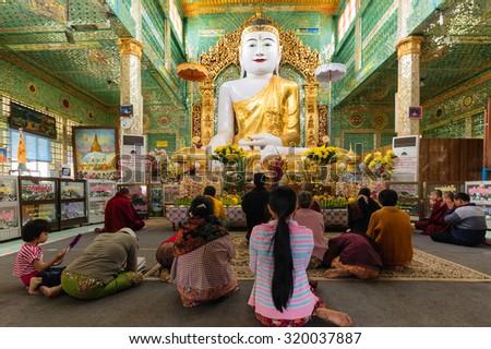 SAGAING, MYANMAR, JANUARY 16, 2015 : People are sitting on the floor for praying the large golden Buddha in the Soon U Ponya Shin Paya pagoda, Sagaing, Myanmar (Burma). - stock photo