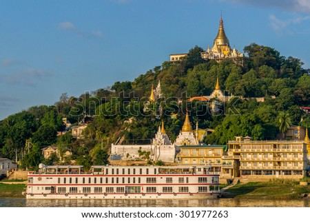 Sagaing, Myanmar - November 19:  A cruise ship stops in front of a temple hill in the old capital Sagaing at sunrise. November 19, 2015 in Sagaing, Myanmar - stock photo