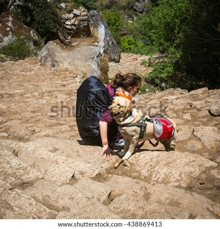 SAGARMATHA, NEPAL-MAY 6: Woman with a dog 6, 2016 in Sagarmatha, Nepal. Woman with a dog on the track to the Everest base camp. - stock photo
