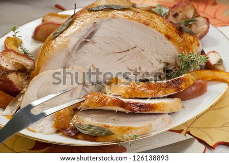 Sage - honey butter rub turkey breast garnished with roasted pumpkin and apples in fall themed surrounding. - stock photo