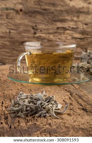 sage tea on wooden table - stock photo