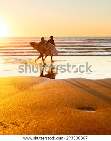 SAGRES, PORTUGAL - DEC 31, 2014: Two surfer running on the beach at sunset. Portugal has one of the best surfing scenes in Europe - stock photo