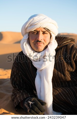 Sahara Desert MOROCCO DEC 31st 2014 : Unidentified two camel-man sits on the sand dune in Sahara Desert while waiting for customers to see last sunset of the year - stock photo