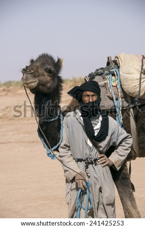 SAHARA DESERT, MOROCCO, MARCH 6, 2014.  A beduin standing with his camel in the spring in the Sahara Desert in Morocco, on March 6th, 2014. - stock photo