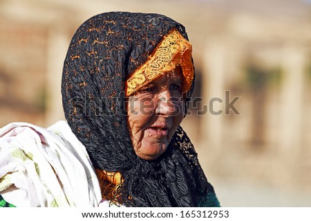 SAHARA DESERT, MOROCCO 19 OCTOBER 2013: Old nomad woman in the Sahara desert, Morocco. Nomadic tribes living in the desert with a traditional lifestyle as a hundred years ago. - stock photo