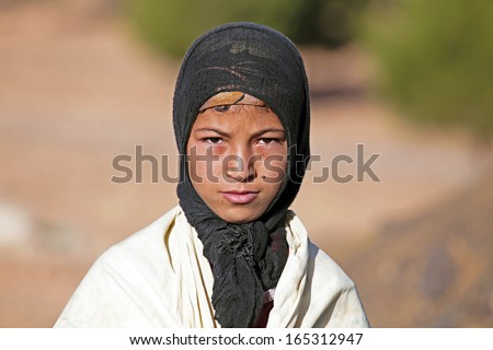 SAHARA DESERT, MOROCCO 19 OCTOBER 2013: Young nomad woman in the Sahara desert, Morocco. Nomadic tribes living in the desert with a traditional lifestyle as a hundred years ago. - stock photo