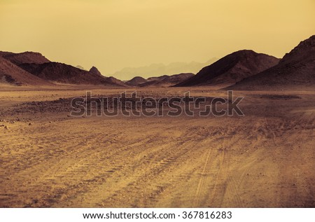 Sahara desert - mountain landscape with dusty offroad and stone hills on a horizon. Exotic adventure or expedition in Arabian desert, extreme travel to Egypt. The Martian landscape in African desert. - stock photo