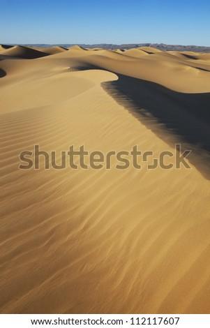 Sahara desert sand dunes with clear blue sky at Erg Lihoudi, M'hamid, Morocco. - stock photo
