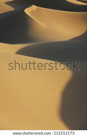 Sahara desert sand dunes with deep shadows at Erg Lihoudi, M'hamid, Morocco. - stock photo