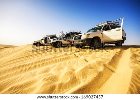 SAHARA, TUNISIA - JUL 10: Driving a 4-wheel drive SUV on the desert, traditional entertainment for tourists on July 10, 2012 in Sahara, Tunisia - stock photo