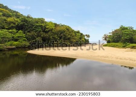 Sahy river view meeting the ocean at Barra do Sahy beach - Sao Sebastiao - Sao Paulo - Brazil - stock photo