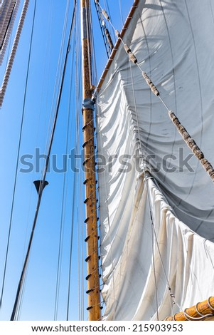 Sail and rigging being hoisted against a clear blue sky. Tall ship schooner at sea.  - stock photo