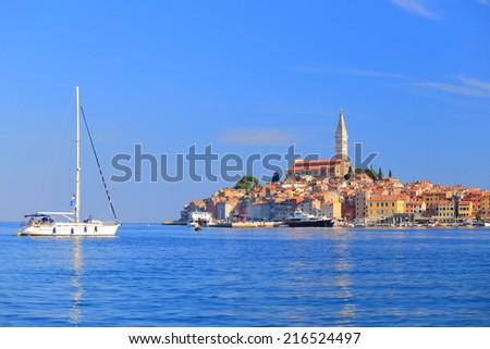 Sail boat enters the harbor of old Venetian town near the Adriatic sea, Rovinj, Croatia - stock photo