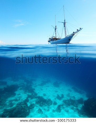 Sail boat in a tropical calm sea on a surface and coral reefs  underwater - stock photo