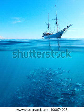 Sail boat in a tropical calm sea on a surface and large school of a Jackfish underwater - stock photo