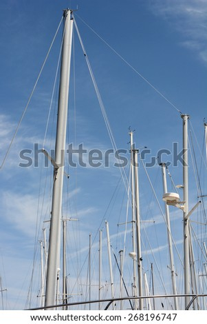 Sail boat masts against a blue sky. Closeup of the masts of boats in storage for the winter, in vertical format. - stock photo