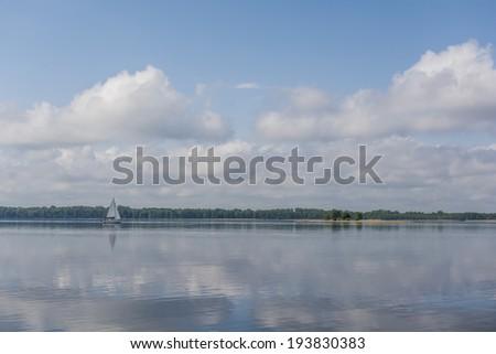 Sail boat on a calm lake - stock photo