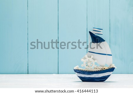 Sail boat Toy model with Ship'wheel, rope and seashell on white and blue wooden background - stock photo