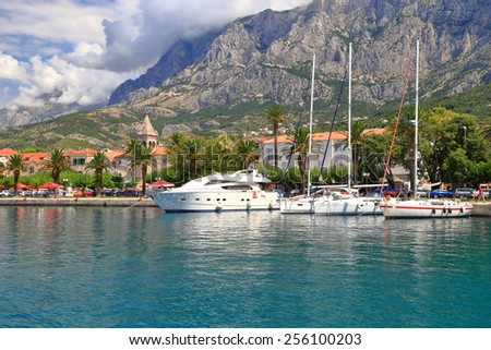 Sail boats by the pier of an old traditional town and harbor, Makarska, Croatia - stock photo