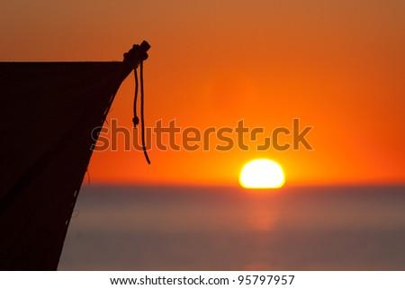 Sail of Vezo dugout at sunset near Tsifota, southwestern Madagascar - stock photo