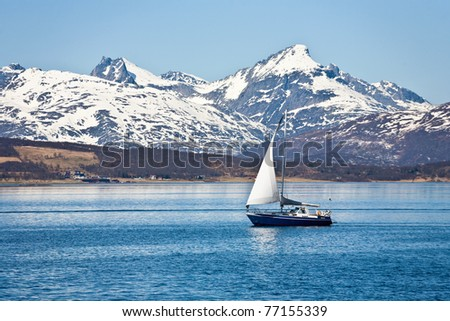 Sailboat and a rocky coastline - stock photo