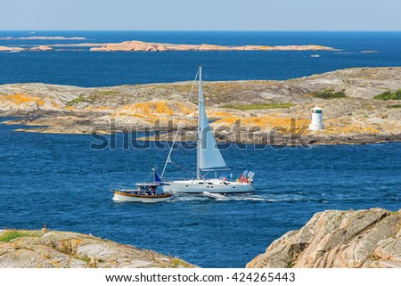 Sailboat and motorboat in the rocky coastal landscape - stock photo