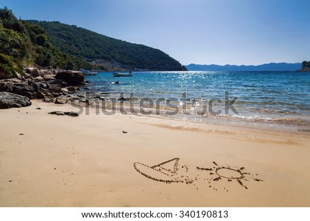 Sailboat and sun drawing in the sand against the sea and island - stock photo