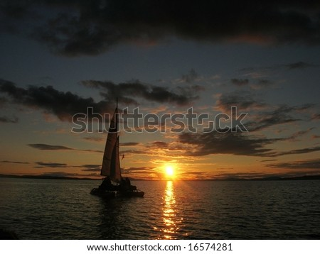 Sailboat at sunset with cloudy sky - stock photo