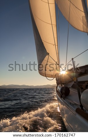 Sailboat crop during the regatta at sunset ocean  - stock photo