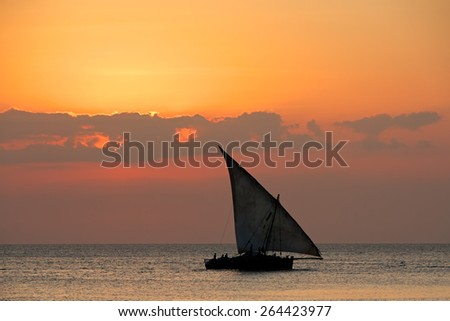 Sailboat (dhow) on water at sunset with clouds, Zanzibar island - stock photo