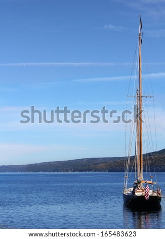 Sailboat docked on the lake with blue sky. - stock photo