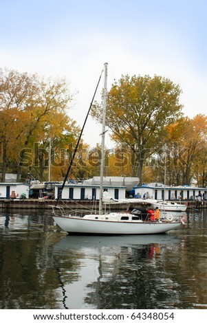 Sailboat entering marina at Ward's Island in Toronto with still calm water in autumn - stock photo
