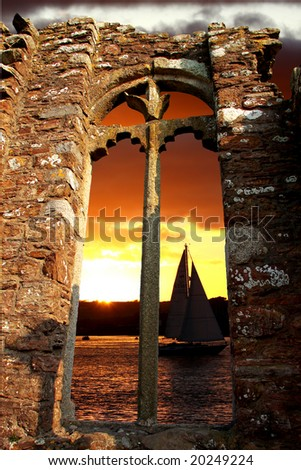 sailboat in golden sunset with a gothic window - stock photo