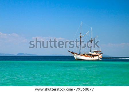 Sailboat in the ocean against blue sky - stock photo