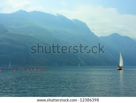Sailboat on Garda lake early hazy morning - stock photo
