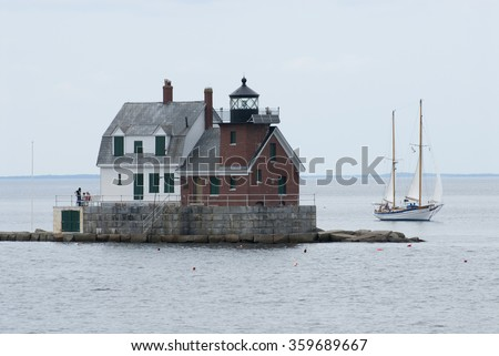Sailboat passes by Rockland Breakwater lighthouse in mid coast Maine during high tide.  - stock photo
