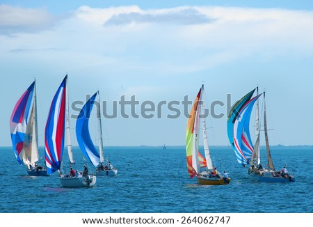 Sailboat regatta race with colorful spinnaker sails up on a beautiful sunny morning. - stock photo