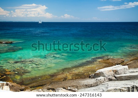 Sailboat sailing near the wild and beautiful cost of Aegean Sea. Photo made on island of Thassos, Greece - stock photo
