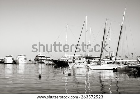 Sailboats anchored in harbor. Beautiful monochromatic photo with yachts are moored in the sea port. Black and white image on vintage style. Luxury lifestyle on summertime and sea vacation.  - stock photo