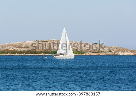 Sailboats at the rocky coastline at summer - stock photo