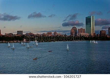 Sailboats in the foreground point towards the Boston skyline - stock photo