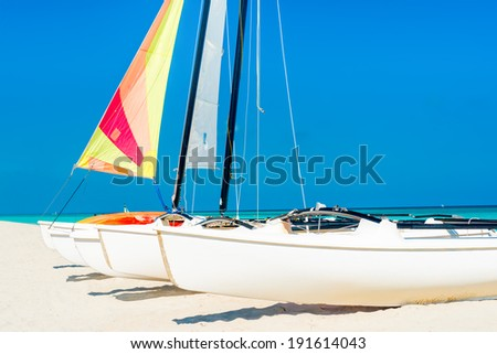 Sailboats with colorful sails on a tropical beach in Cuba - stock photo
