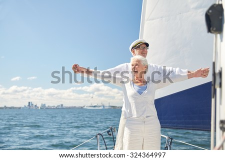 sailing, age, tourism, travel and people concept - happy senior couple enjoying freedom on sail boat or yacht deck floating in sea - stock photo