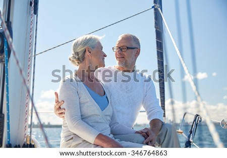 sailing, age, tourism, travel and people concept - happy senior couple hugging and talking on sail boat or yacht deck floating in sea - stock photo